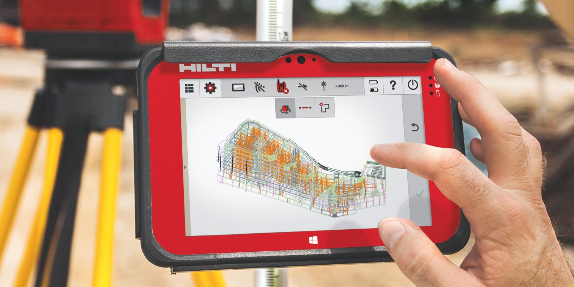 Two workers onsite using a Total Station layout tool and BIM-ready tablet to position MEP supports
