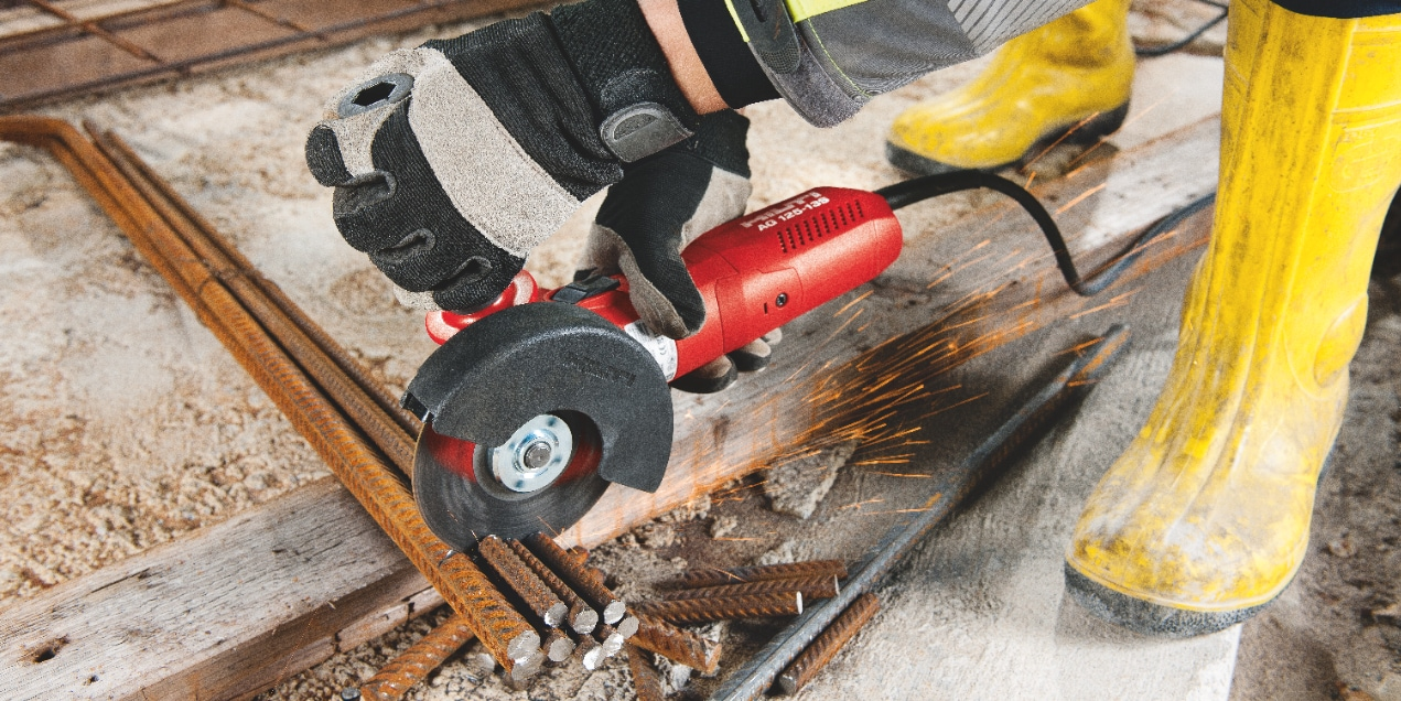 Construction worker using an angle grinder to cut rebar