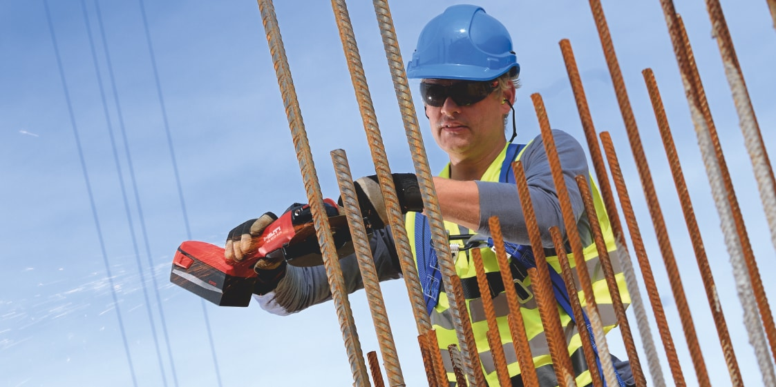 Construction worker cutting rebar using a AG 600-A36 Cordless angle grinder with Active Torque Control (ATC) to help prevent kickback