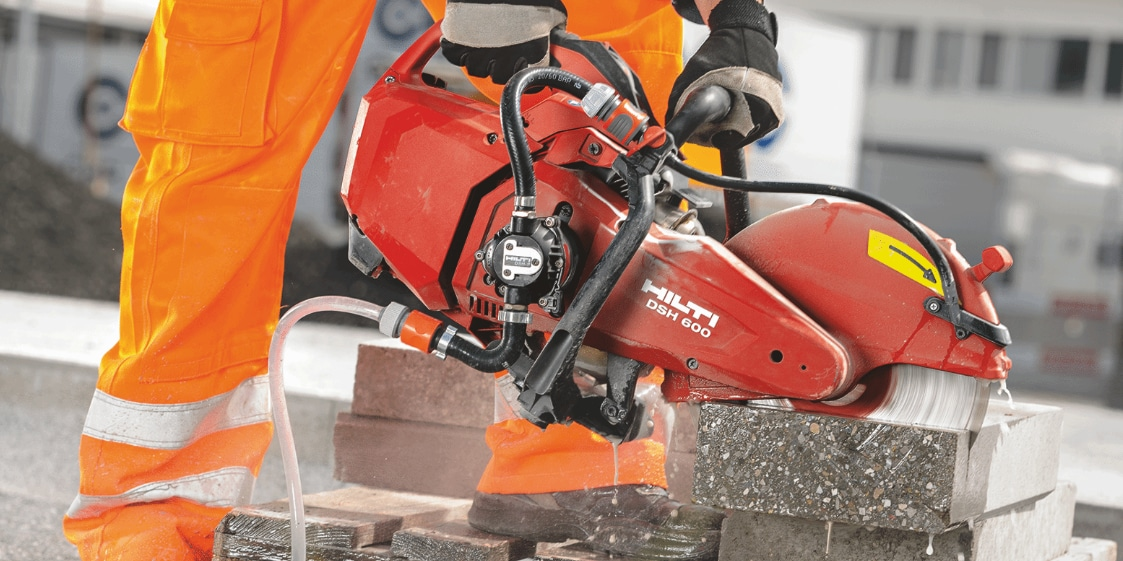 Construction worker cutting concrete using a DSH 600-X Gas saw which comes with a quick-acting brake