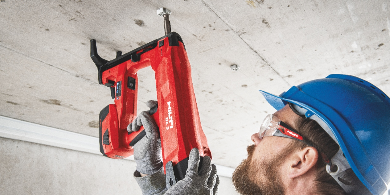 BX 3 battery-powered nailer, a low vibration alternative to drilling, being used to fasten on concrete